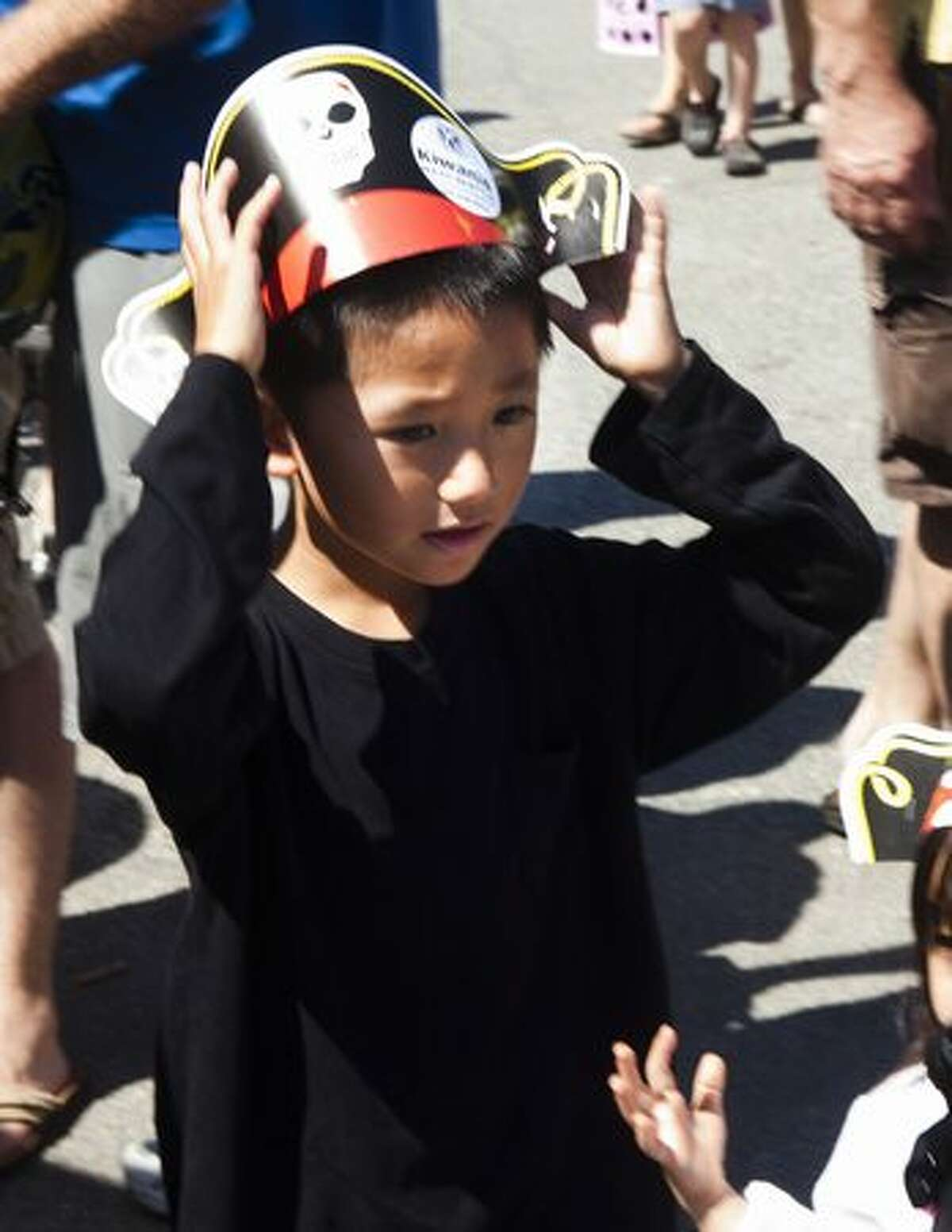A boy adjusts his free pirate hat, given out by the Kiwanis Club.