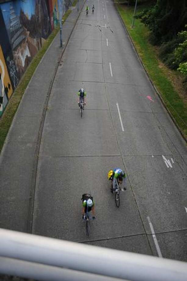 Cyclists ride under a bridge on 40th St. as they start their trip to Portland. Photo: Elliot Suhr, Seattlepi.com