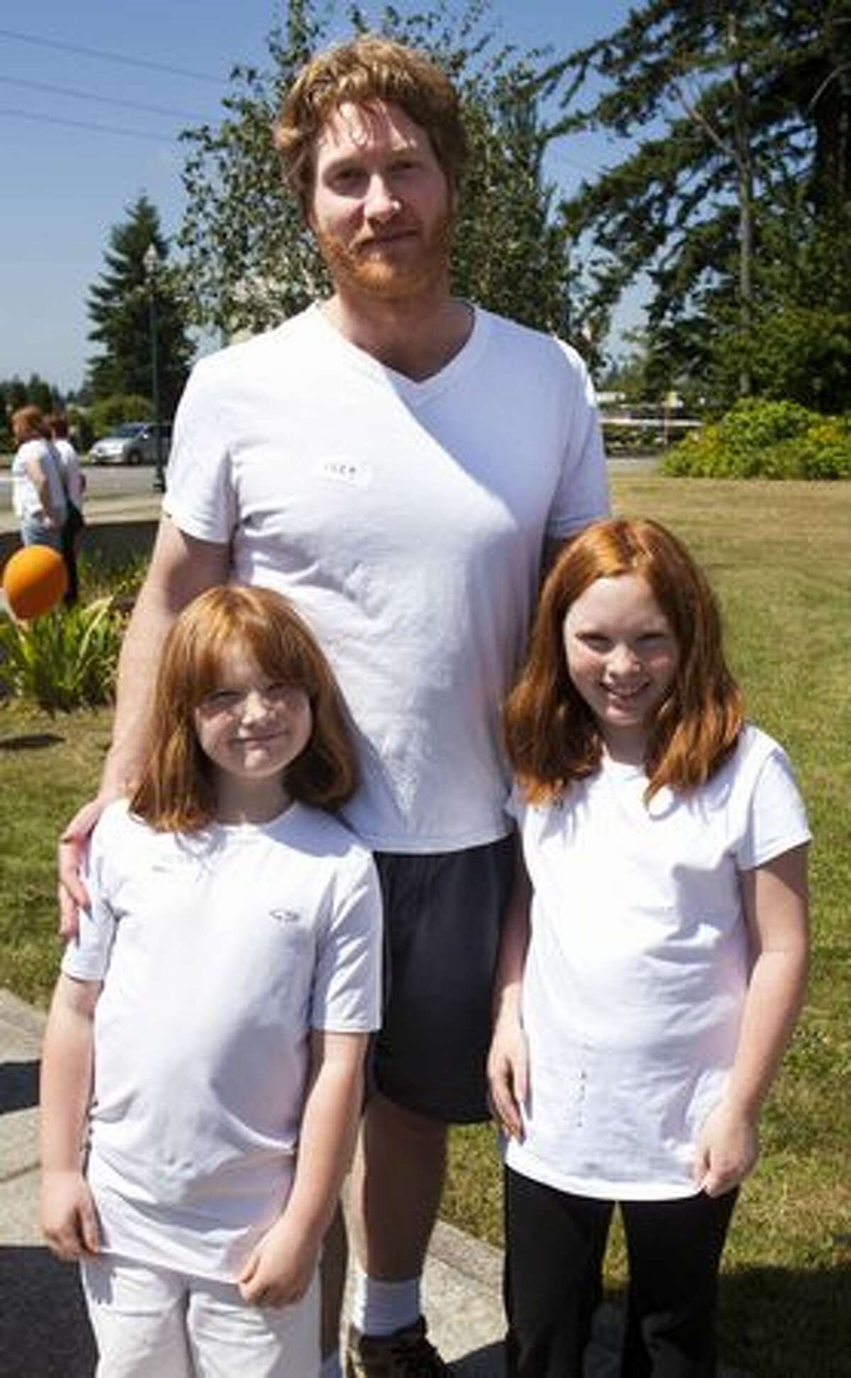Molly, 7, Megan, 10, and Rob McAdams wait in line for Redheads and More Redheads Day.