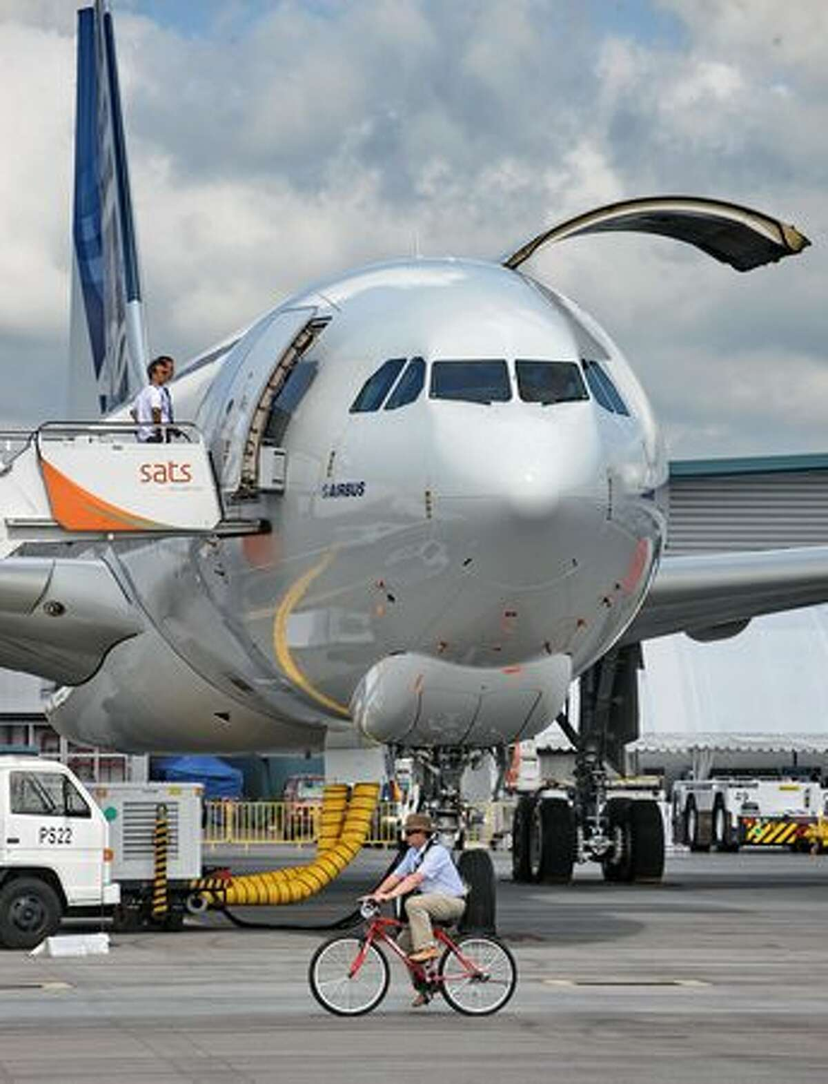 A cyclist rides past an Airbus A330-200F cargo plane for the static display at the Singapore Airshow on Feb. 1, 2010.