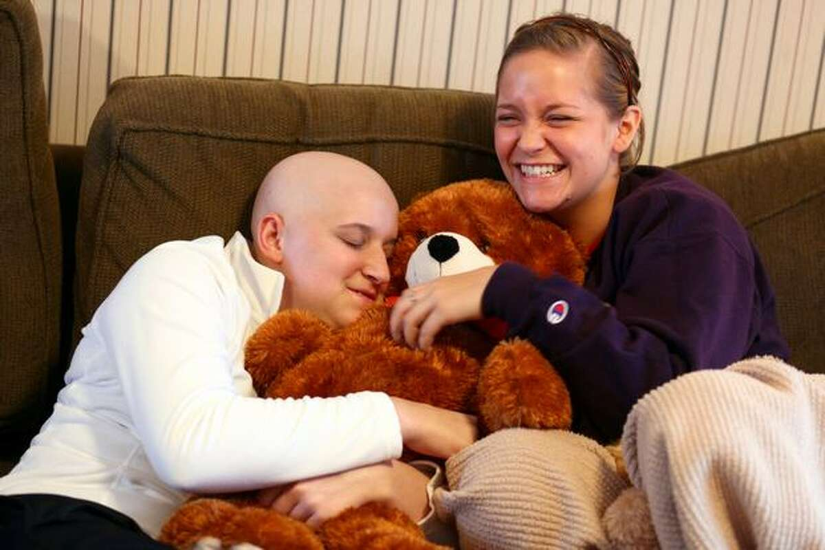 Ashley Aven, left, hugs a bear given to her by former softball teammate Stephani Bernard in Ashley's Lynnwood home. Ashley, 17 years-old and a softball player at Meadowdale High School, is battling acute myeloid leukemia, a rare and aggressive disease. In early January doctors gave her 2 months to live; she has been putting up a strong fight against the aggressive disease.
