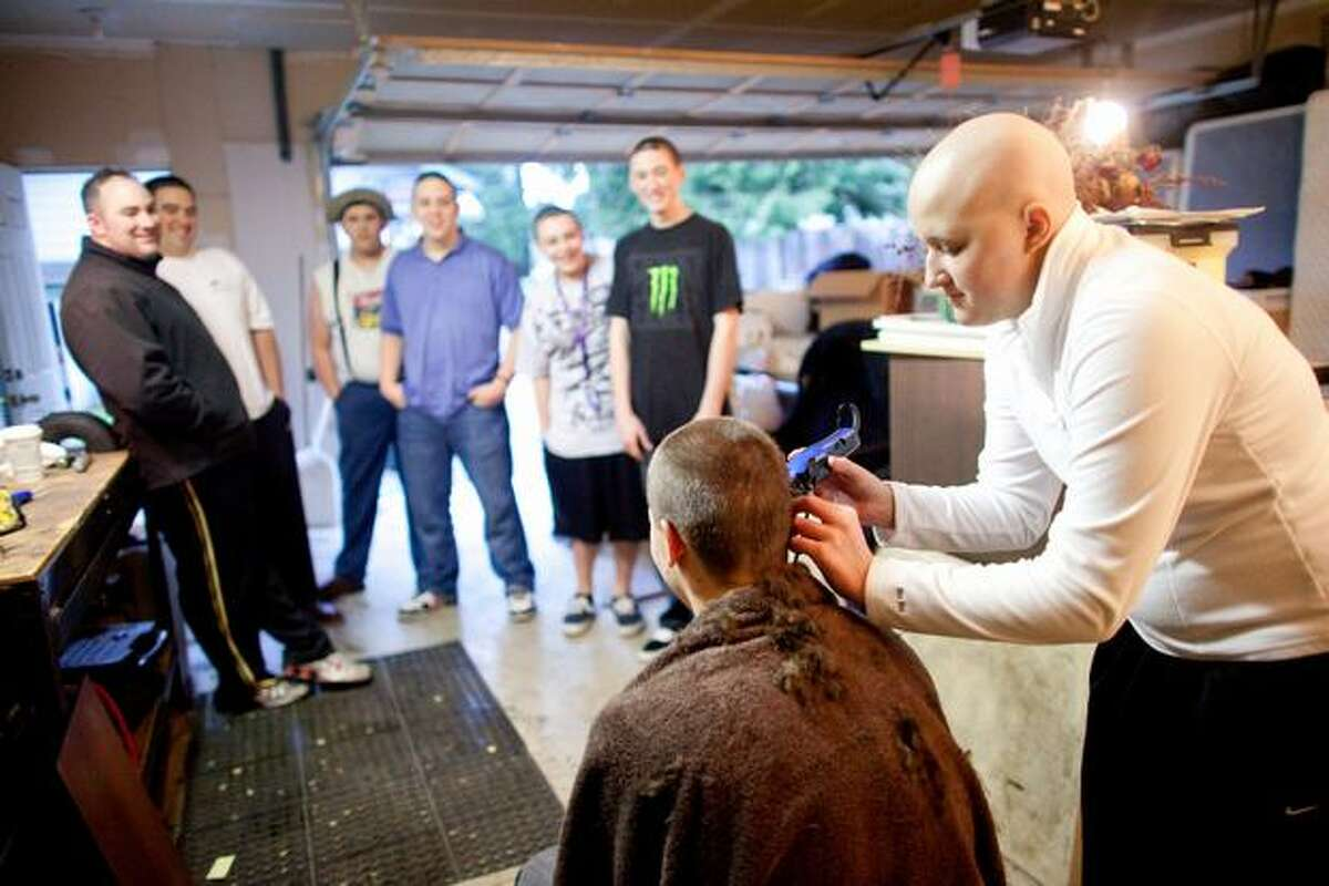 Ashley Aven shaves the head of friend Cody Kendrick, 15, in the Aven family garage in Lynnwood. Ashley, 17 years-old and a softball player at Meadowdale High School, is battling acute myeloid leukemia, a rare and aggressive disease. In early January doctors gave her 2 months to live; she has been putting up a strong fight against the aggressive disease.