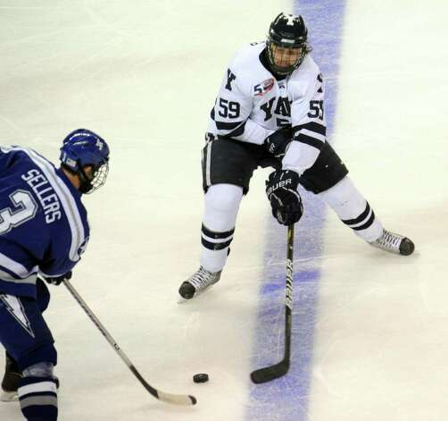 Highlights from NCAA hockey tournament action between Yale and Air Force at the Webster Bank Arena at Harbor Yard in Bridgeport on Friday March 26, 2011. Yale's #59 Chad Ziegler tries to intercept the puck from Air Force's #3 Brad Sellers, left. Photo: Christian Abraham / Connecticut Post