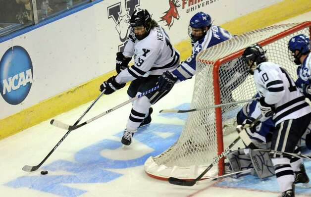 Highlights from NCAA hockey tournament action between Yale and Air Force at the Webster Bank Arena at Harbor Yard in Bridgeport on Friday March 26, 2011. Yale's #19 Denny Kearney, top left, as Air Force's #6 Adam McKenzie blocks. Photo: Christian Abraham / Connecticut Post