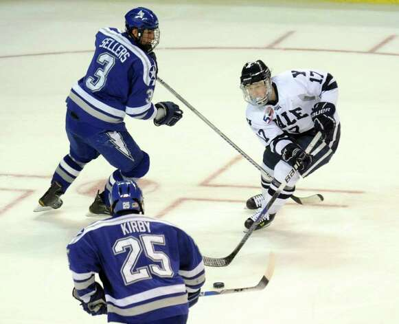 Highlights from NCAA hockey tournament action between Yale and Air Force at the Webster Bank Arena at Harbor Yard in Bridgeport on Friday March 26, 2011. Yale's #17 Andrew Miller, right, looks to take the puck between Air Force's #25 Tim Kirby and #3 Brad Sellers, top left. Photo: Christian Abraham / Connecticut Post