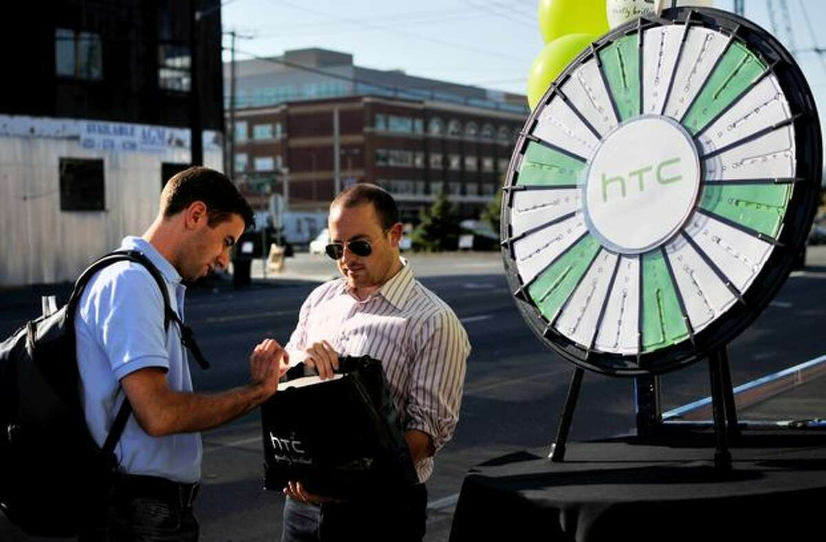Rickey Bird gives Michael Delisi several grab-bag options after Delisi spun the HTC prize wheel at the entrance of gdgt live in Seattle.