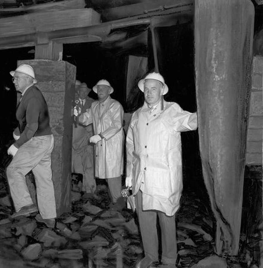 City Engineer W. E. Parker, right, stands beside damaged piling behind seawall along Alaskan Way, where teredos (wood-boring worms) ate into a number of pilings. Exact date unknown. Photo: P-I File