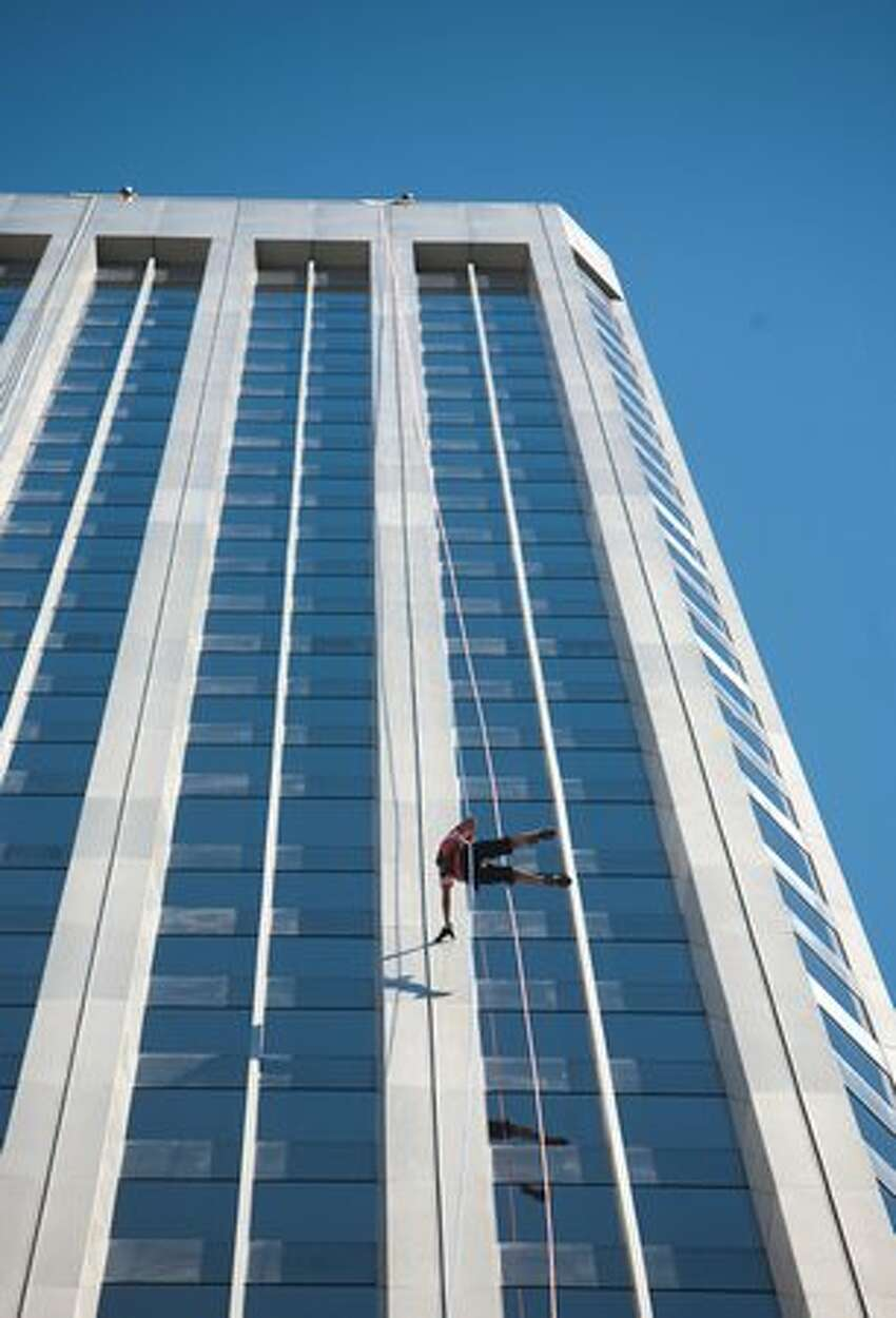 A rappeller reaches out to touch the building during