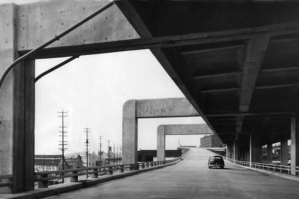 The March 1952 photo caption read: Looking north along the viaduct near Lenora Street where the lower deck carrying southbound traffic edges under the top northbound deck. Note the beauty that the giant concrete supports add to the viaduct.