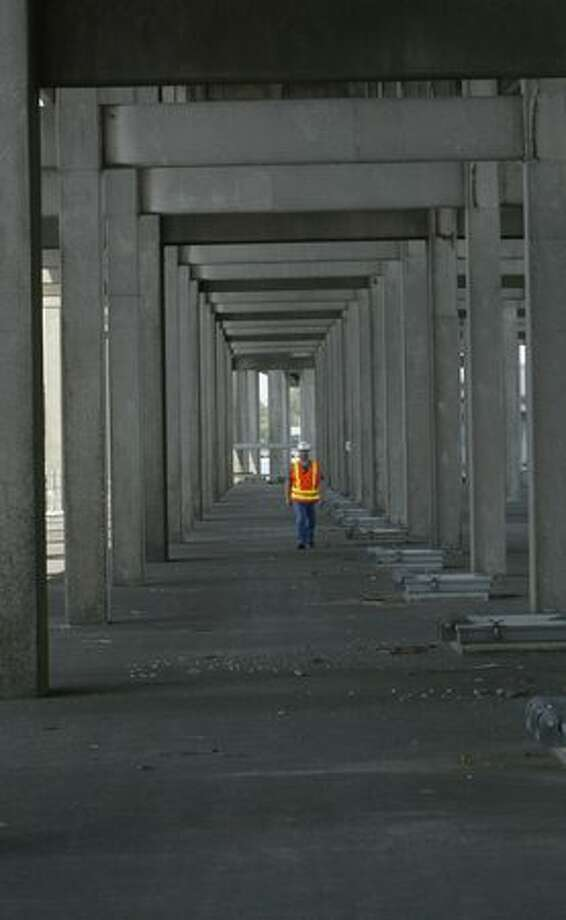 The July 2007 photo caption read: Rick Rodda, assistant superintendant of the 520 project, walks along the area under the roadway at the west end of the bridge. He's showing how much space there will be between the pontoons and the roadway on the new bridge when its built. Photo: P-I File