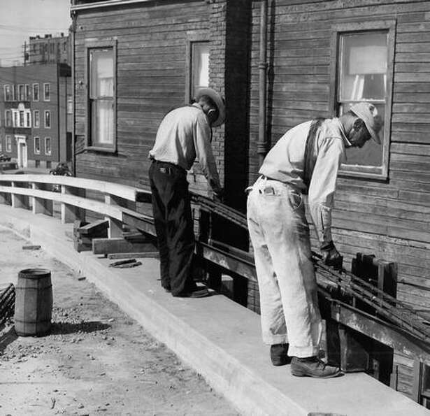 The April 26, 1951 photo caption read: Workmen on new multi-million dollar Alaskan Way Viaduct place