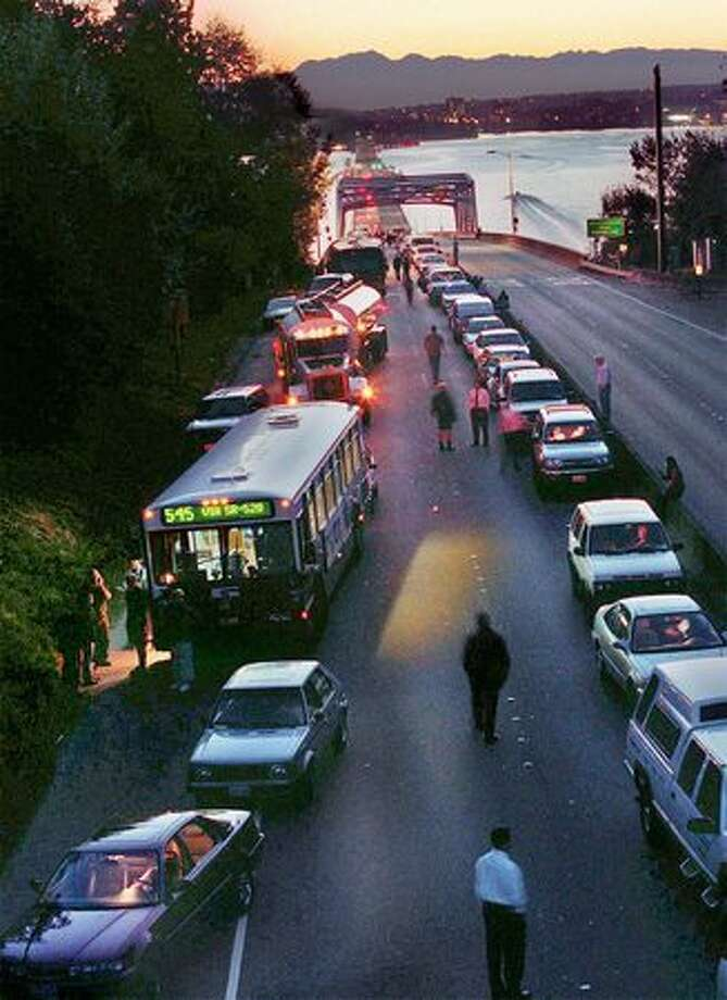 Peoplestranded on state Route 520 near the bridge after a bomb threat was made on the bus, September 2000. Photo: P-I File