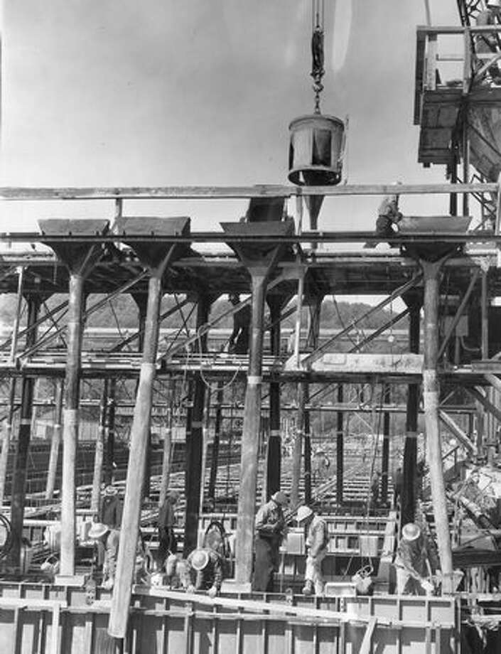 The May 1961 photo caption read: In a graving dock on Marginal Way Southwest yesterday, the first concrete came down these chutes for pontoon No. 1 of the second Lake Washington bridge. Photo: P-I File