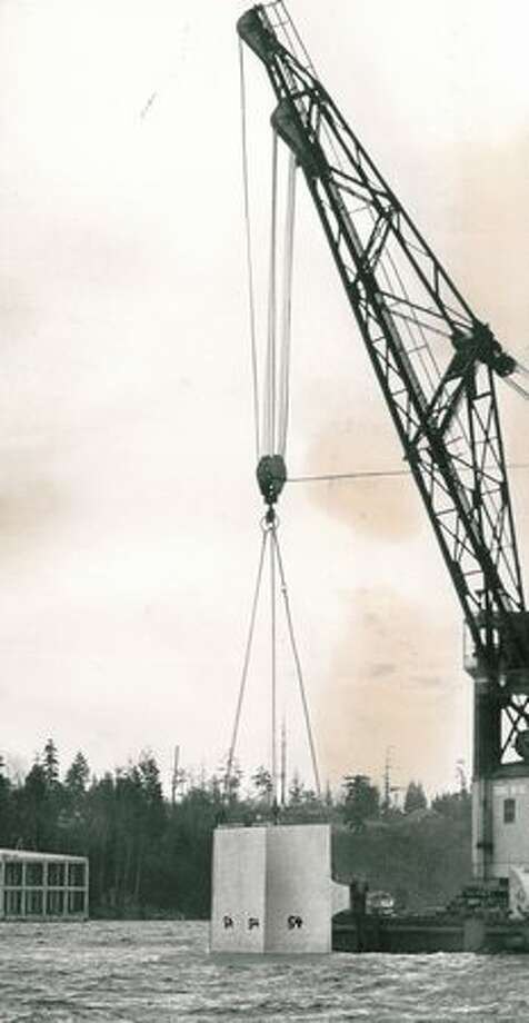 The March 1963 photo caption read: A crane lowers an anchor near eastern end of second Laking Washington floating bridge yesterday in delicate maneuver. Photo: P-I File