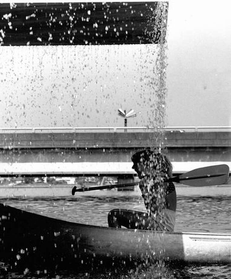 Amy Smidt canoes into the spill-off water of the fountains on Lake Washington, near the 520 bridge., May 1989. (Phil H. Webber/Seattlepi.com file). Photo: P-I File