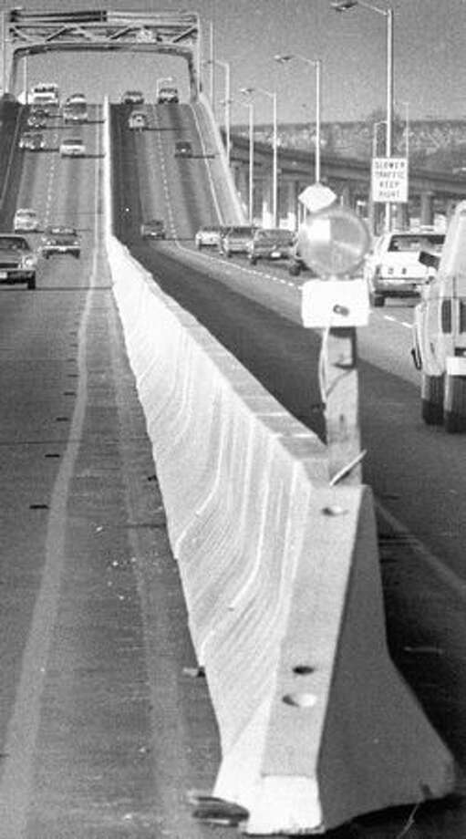 The December 1974 photo caption read: Safety divider strips slowly but surely increase along the length of the Evergreen Point Bridge. They are being installed by the State Highway Dept. Photo: P-I File