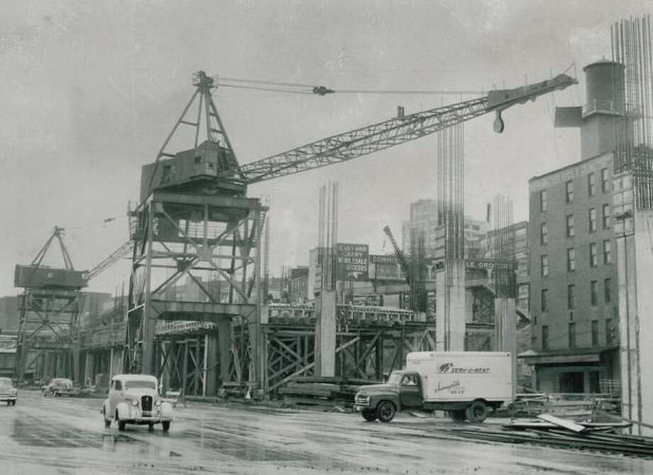 The May 1951 photo caption read: There's a real big show underway along the waterfront where the Alaskan Way Viaduct is being constructed, and these two 5-story-high cranes straddle railway switching tracks. Photo: P-I File