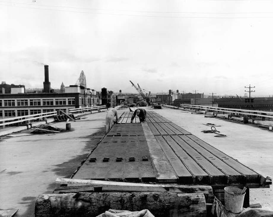 The March 4, 1952 photo caption read: Casting concrete rails for guard fence. Work is done on job as construction advances. Photo: P-I File