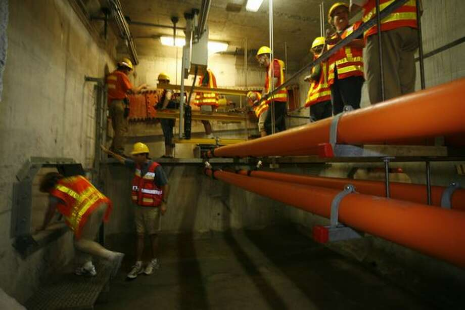The July 14, 2007 photo caption read: Jim Stonecipher, upper left, explains how the anchor cables work to visitors touring the inside of a pontoon. The State Department of Transportation invited about 50 local politicians, DOT employees, seven winners of a drawing for the tour and the media to tour the maintenance work being done on the 520 floating bridge. Photo: P-I File