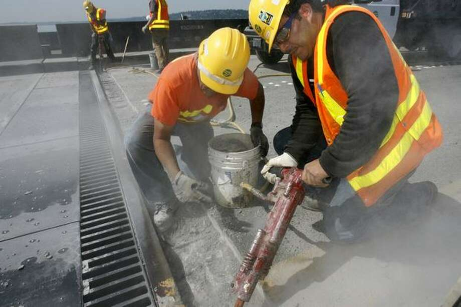 The July 2007 photo caption read: Guillermo Arreguin, right, and Jim Rockett, remove concrete to make repairs to finger joints in an expansion plate. The fingers failed so they have to get down to good concrete and then install epoxy anchors. In the backgrond is Bruce Watkins, left, and Mark Epstein. Photo: P-I File
