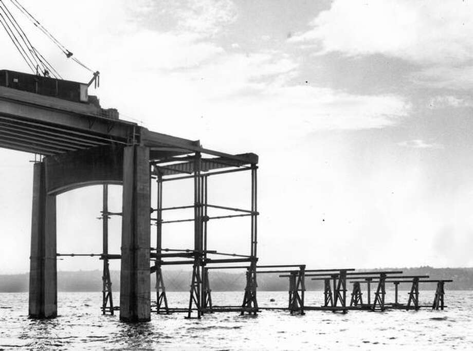 The November 1962 photo caption read: Falsework, which will support temporarily the steel truss structure over the east ship canal section of the second Lake Washington bridge, reaches out ahead of steel workers. Photo: P-I File