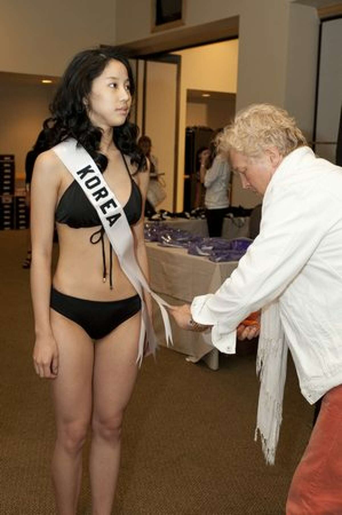 Joori Kim, Miss Korea 2010 gets her country sash as she starts the registration and fitting process.