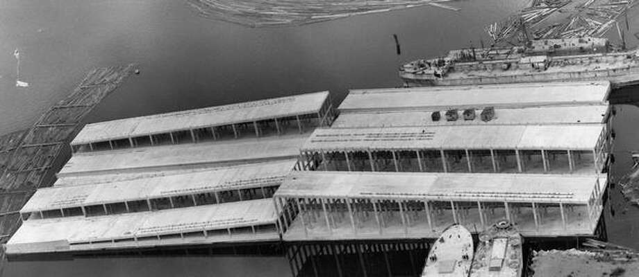 The May 1962 photo caption read: Sections of the Evergreen Point bridge reach out onto Lake Washington at the Kennydale approach, and right on schedule. The lake's second floating bridge is expected to be complete in June, 1963 the target date. Photo: P-I File