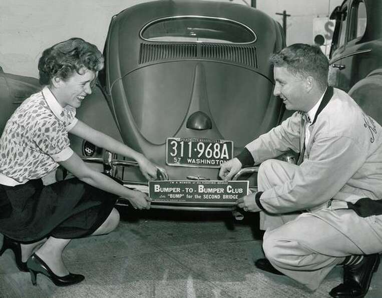 The August 1957 photo caption read: Jaye Farrell and Pat Biggs attach a bumper sign identifying car