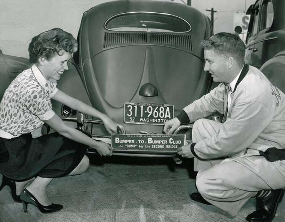 "The August 1957 photo caption read: Jaye Farrell and Pat Biggs attach a bumper sign identifying car as belonging to a member of the Floating Bridge Bumper-to-Bumper Club. ""Let's 'Bump' for the Second Bridge,"" is its message. Photo: P-I File"