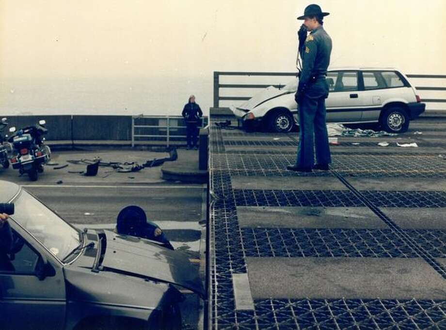 The December 1989 photo caption read: A state trooper stands on the end of the span that rose five feet yesterday, causing cars to slam into it. Photo: P-I File