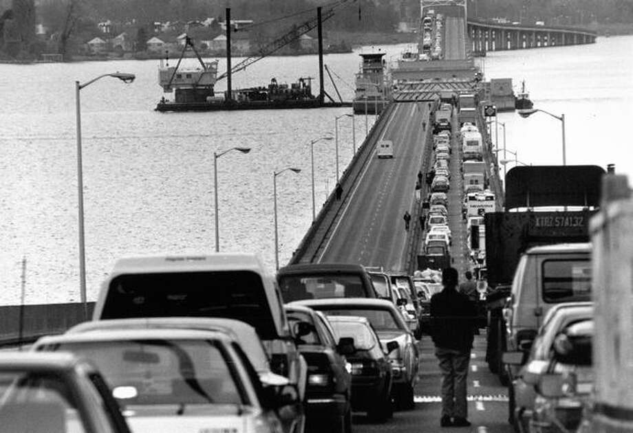 The November 1990 photo caption read: The Evergreen Point Bridge draw span was useful in getting equipement to the site of the Interstate 90 bridge sinking. Photo: P-I File