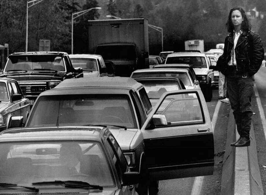 The November 1990 photo caption read: Tom Bray of Seattle stands on a lane divider on an approach on the Evergreen Point Bridge while waiting for the barges to pass. Photo: P-I File