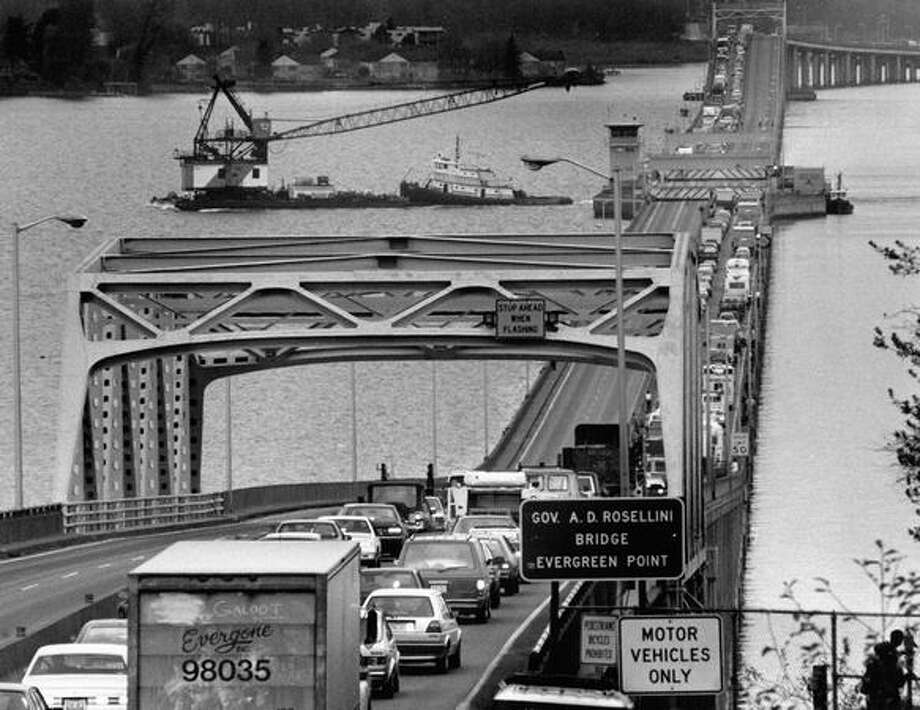 Vehicles wait on the Evergreen Point Bridge while the span is open to allow barges hauling cranes to go through on their way to the I-90 bridge, November 1990. Photo: P-I File