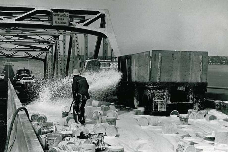 Firefighters spray foam on scattered chemical containers that tumbled from a truck on the 520 bridge, August 1980. Photo: P-I File