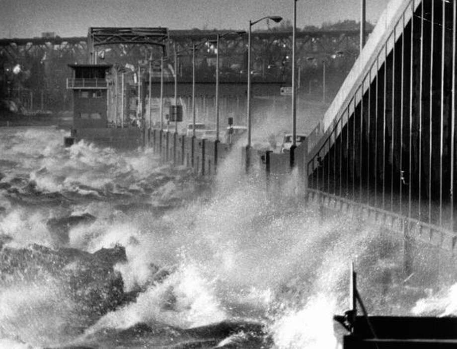 The December 1975 photo caption read: Gales sent waves crashing over the Evergreen Point Floating Bridge yesterday, endangering motorists. Photo: P-I File
