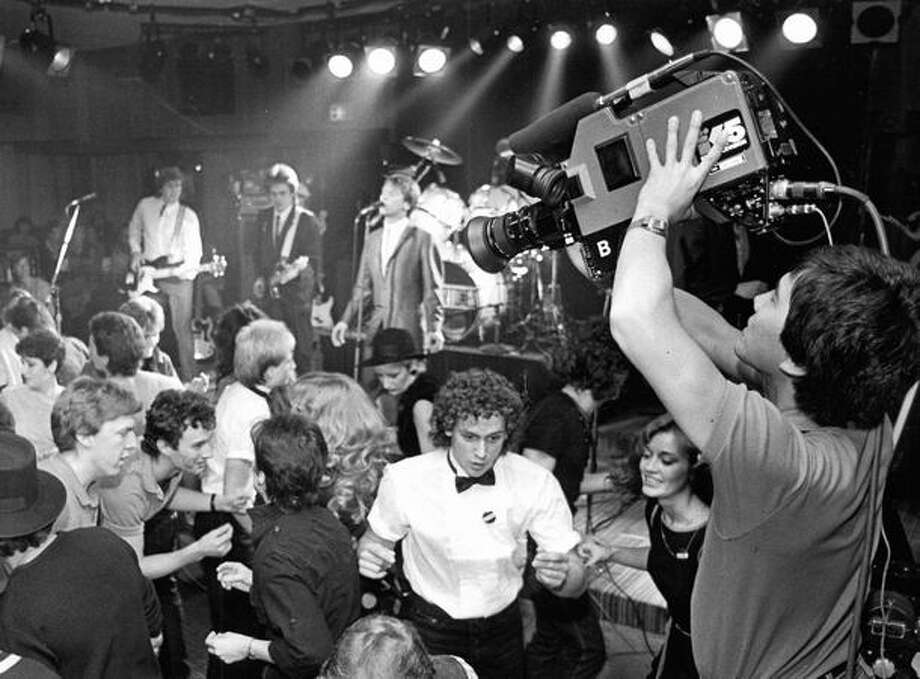 KING/5 cameraman Darrel Suto raised his camera above his head for a shot of peope dancing at Astor Park as the Eagertones play on Oct. 11, 1983. (Kurt Smith/Seattlepi.com file) Photo: P-I File