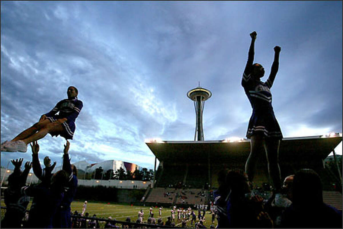 Garfield High School cheerleaders go through their routines while the Bulldogs football team battles Franklin last night in the shadow of the Space Needle.