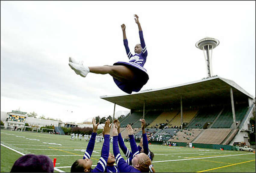 Garfield High School cheerleaders toss junior Zakiya Linzsey as they practice their routines prior to their game with Franklin at Memorial Stadium in the shadow of the Space Needle.