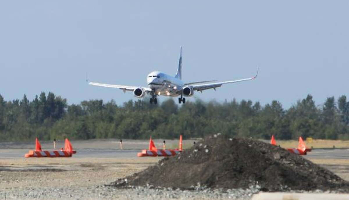 An Alaska Airlines plane lands near one of the construction projects at Bellingham International Airport.