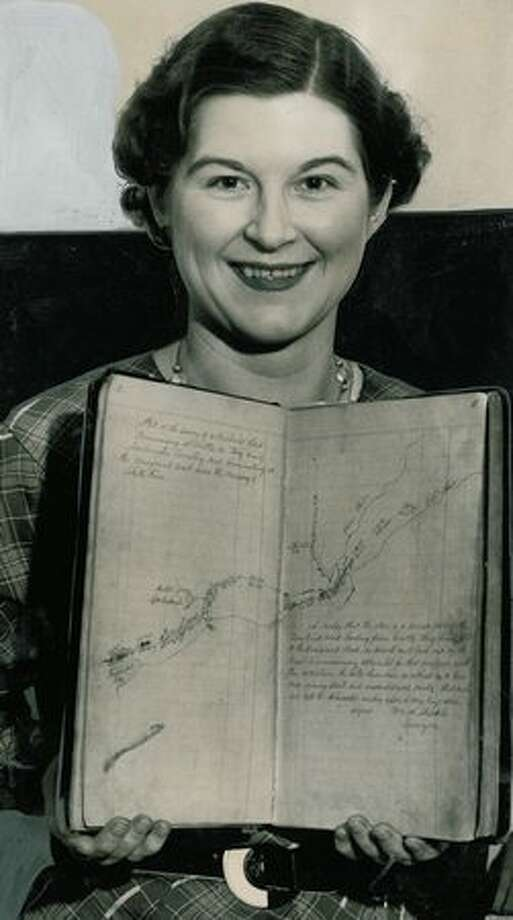 The December 1934 photo caption reads: Gertrude B. Conner with King County's road survey book No. 1, which was made in 1854 by a party of pioneers blazing Seattle's first highway through the wilderness. Photo: P-I File