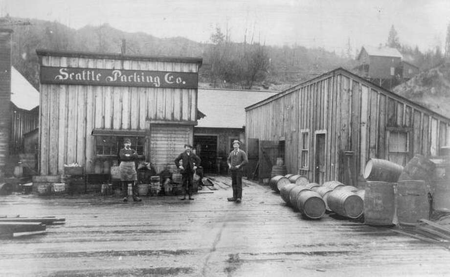The caption for this 1891 photo reads: The barrel was important to the Seattle Packing Company of that day, and so were wooden shoes ...  If you look closely you will find that the three men have adopted the Holland footgear to Puget Sound. Photo: P-I File