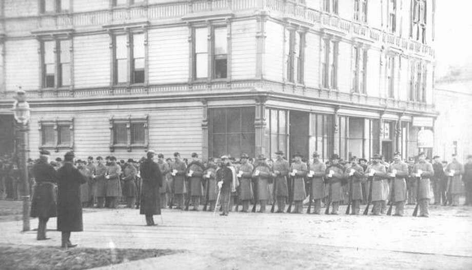 The caption for this 1886 photo reads: U.S. Soldiers in Seattle during anti-Chinese riots. This photo is of the 14th Infantry answering roll call on Front Street, now First Avenue. Photo: P-I File