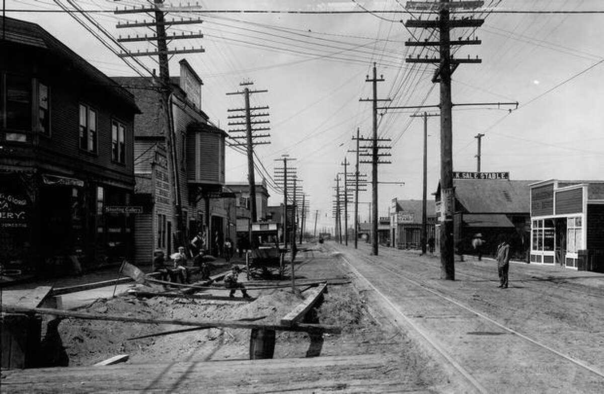 The photo caption reads: Here is a stretch of the Georgetown District in 1908, occupied by two livery stables, two lumber sheds, a paint shop, a milk depot (at far right) and a feed store. In the left foreground a bit of early day street improvement is under way - the planking is being replaced. The kids sit in front of a shooting gallery, and the man by the telephone pole at right is waiting for a street car to take him in to 'town.'