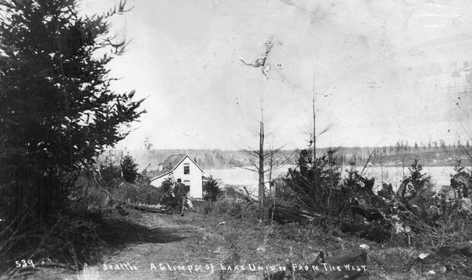 The caption for this 1890 photo reads: In 1889 Mary and Thomas O'Meara brought their little family to Seattle and a year later purchased this cozy home facing Lake Union. Tom O'Meara is coming up the road with a can of fresh milk. Photo: P-I File