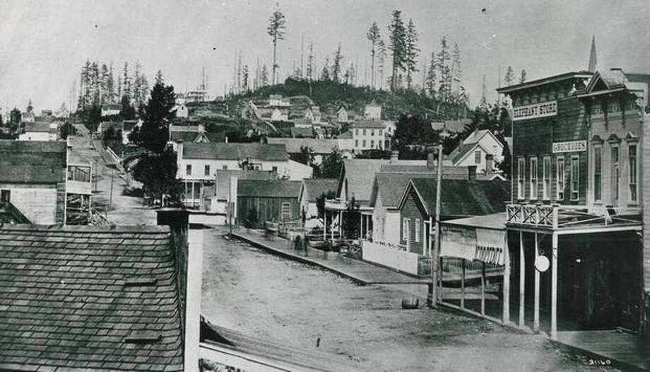 The caption for this photo reads: Looking north on Front Street (now First Avenue) from Cherry Street at Seattle's wooden buildings and wooded hills in the 1860s. Photo: P-I File
