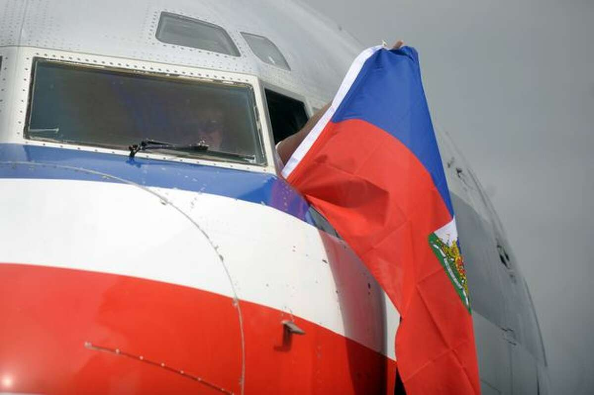 One of the pilots of an American Airlines flight coming from Miami waves a Haitian flag from the cockpit window upon arrival to Port-au-Prince's international airport on Feb. 19, 2010. The first passenger plane to arrive in Haiti since the Jan. 12 earthquake touched down in Port-au-Prince to a warm welcome Friday, but with many passengers carrying a heavy emotional load.