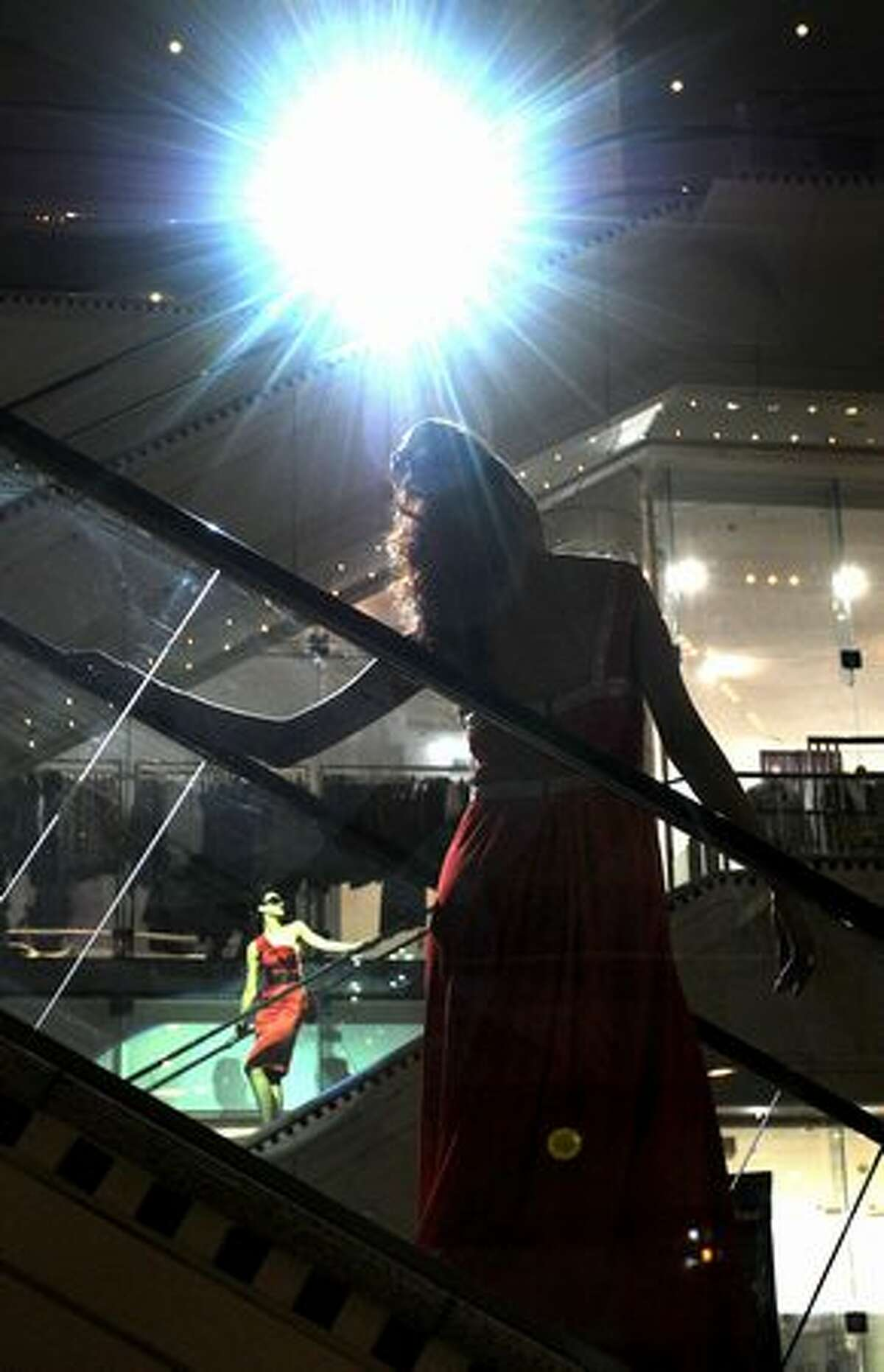 Models parade outfits on an escalator during a show of designers at the Collins234 shopping complex.