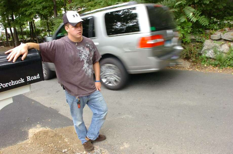Conor Laux photographed along a narrow stretch of North Porchuck Road Thursday afternoon, Sept. 10, 2009. Laux is concerned over traffic safety in the Porchuck Road area, he's had about 10 near misses this summer because of a blind spots at this particular spot in the road. Photo: Keelin Daly / Greenwich Time