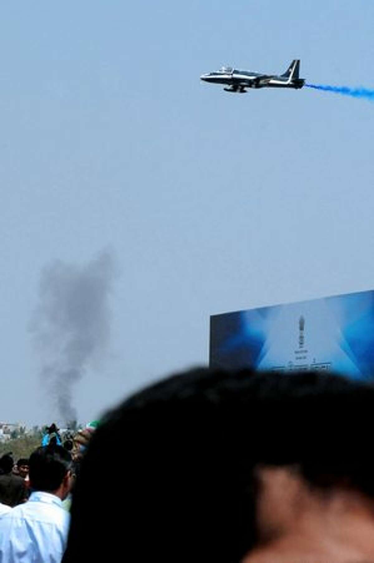 An aircraft of The Indian Naval Aerobatic Team 'Surya Kiran' flies over rising smoke after a colleague crashed an aircraft during the India Aviation 2010 show at Begumpet Airport in Hyderabad on March 3, 2010. A navy aircraft taking part in an acrobatics show on the first day of an air show in the southern Indian city. The plane, a two-seater Kiran MK-II built by the state-run Hindustan Aeronautics, was part of a four-plane formation when it crashed. The accident occurred on the opening day of the India Aviation 2010 show, a five-day civil aviation exhibition.