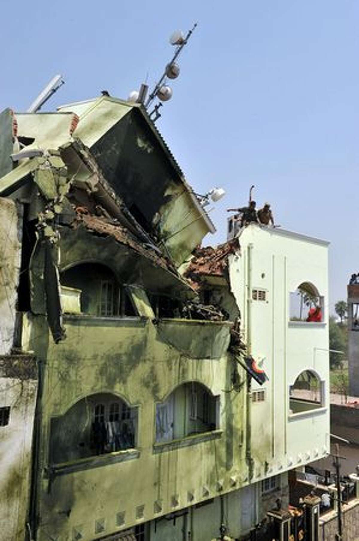 Indian residents and rescue officials search the wreckage of a building after an Indian Naval aircraft from the Aerobatic Team 'Surya Kiran' crashed during the India Aviation 2010 show at Begumpet Airport in Hyderabad on March 3, 2010. A navy aircraft taking part in an acrobatics show on the first day of an air show in the southern Indian city. The plane, a two-seater Kiran MK-II built by the state-run Hindustan Aeronautics, was part of a four-plane formation when it crashed. The accident occurred on the opening day of the India Aviation 2010 show, a five-day civil aviation exhibition.